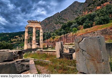 Ruins Of Tholos Of Ancient Greek Goddess Athena Pronaia In Delphi, Greece. Three Doric Columns, Moun