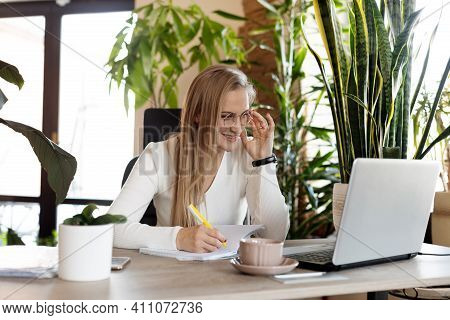 A Beautiful Business Woman Works At A Laptop In The Office And Makes Notes In A Notebook. Business,