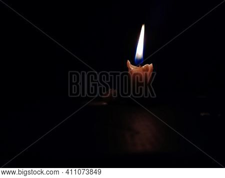 Stock Photo Of A Burning Little White Color Candle With Calm Yellow And Blue Color Flame With Dark B