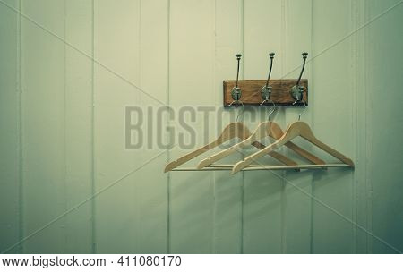 Brown Wooden Cloth Hanger Hanging On Metal Hook On White Wooden Wall Background. Empty Coat Hanger I