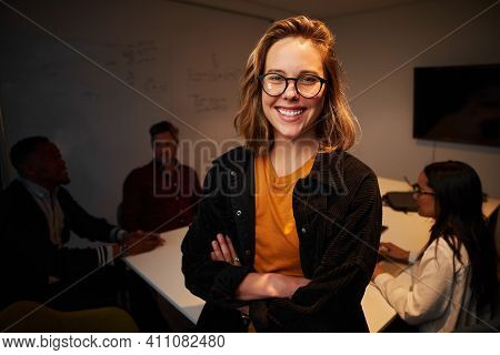 Portrait Of A Smiling Young Confident Businesswoman In Front Of Her Colleagues Sitting At Desk