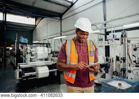 Smiling Young African Male Employee Using Digital Tablet While Working In Industry