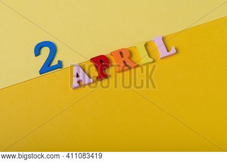 Wooden Letters The Second Of April On A Yellow Background.
