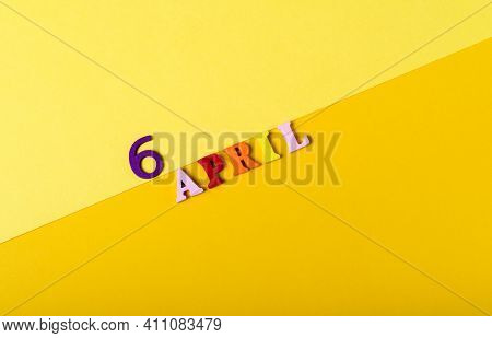 Wooden Letters Of The Sixth Of April On A Yellow Background.