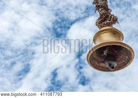 A Hindu-temple Bell Shining On A Cloudy Day.
