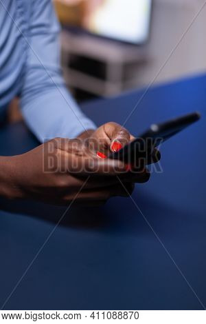 Close Up Of Black Woman Hands Telecommuting Late At Night From Living Room Sitting At Desk. Employee