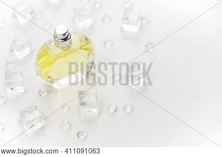 Female Perfume Yellow Bottle, Objective Photograph Of Perfume Bottle In Ice Cubes And Water On White