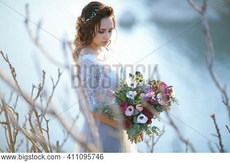 Beautiful Bride In Wedding Dress On The Mountain Top. Stunning Young Bride With Curly Hair And A Bou