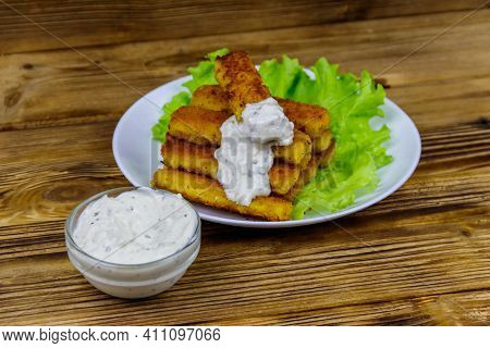 Fried Fish Fingers On A Plate With Lettuce And Tartar Sauce On Wooden Table