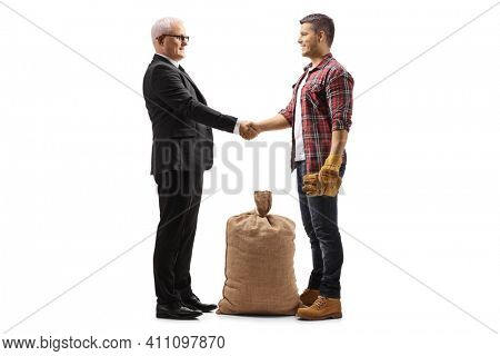 Full length profile shot of a farmer with a burlap sack shaking hands with a mature businessman isolated on white background