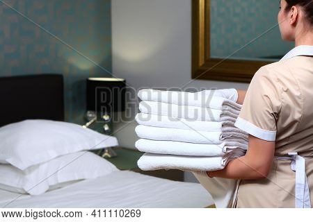 Change Of Towels In The Hotel Room. A Uniformed Maid Cleans The Room. Towels In The Hands Of The Mai