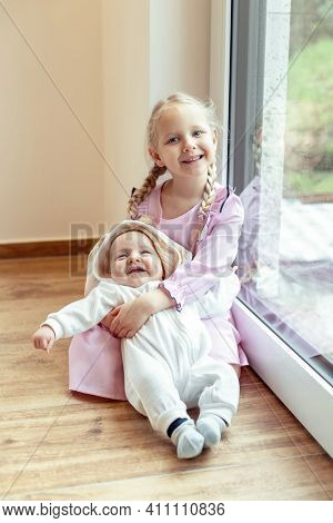 The sister holds the younger brother in her arms