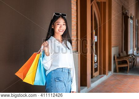Portrait Of Asian Shopaholic Woman Smiling And Wearing Sunglass Headband With Many Colorful Shopping