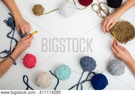 Different Colored Balls Of Yarn. Childrens Hands Are Crocheted And Thread View Frome Above With Plac