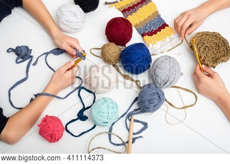 Different Colored Balls Of Yarn. Childrens Hands Are Crocheted And Thread View Frome Above