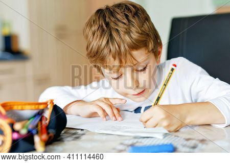 Hard-working School Kid Boy Making Homework During Quarantine Time From Corona Pandemic Disease. Chi