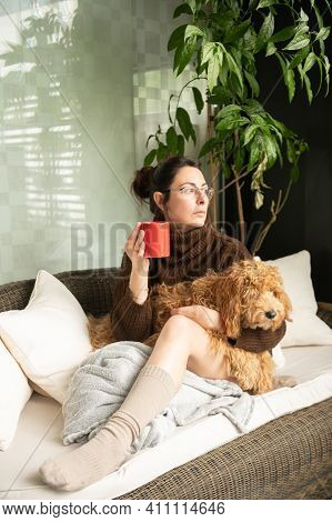 Young And Attractive Girl Sitting Comfortably On A Couch Hugging Her Adorable Dog While Holding A Cu
