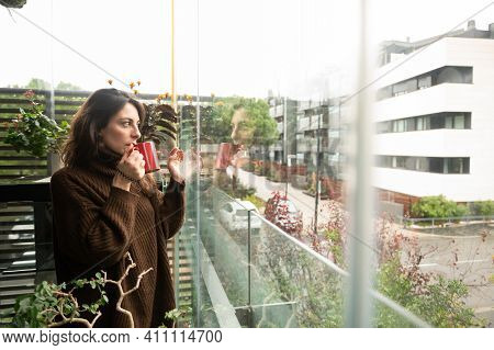 Side View Of Young And Pretty Girl Contemplating The City Through The Window Of Her House While Havi
