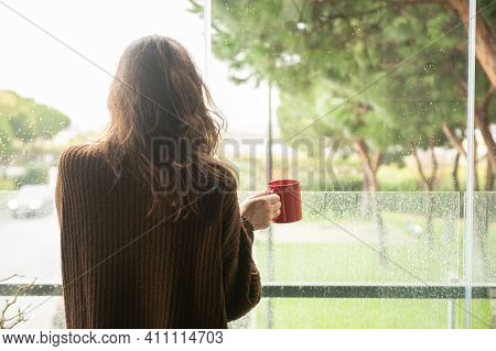 Woman Viewed From Behind Holding A Red Cup Of Coffee In Her Hand Looking Out The Window.copy Space.r