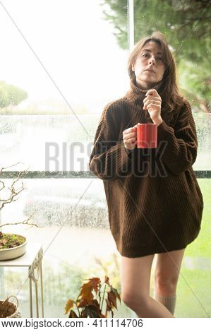Portrait Of Sexy Young Woman Holding A Cup Of Coffee Leaning Against The Window Of Her House, Lookin
