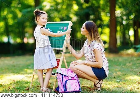 Happy Little Kid Girl And Mother By Big Chalk Desk Preschool Or Schoolkid On First Day Of Elementary