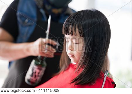 Girl Closed Eyes On Chair At Hairdresser. Children Cut Hair To School. Kids Cut The Bangs. Blur Barb