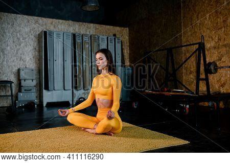 Beautiful Girl In A Yellow Sportswear Is Doing In Yoga, Breathing Correctly. Modern Sports Hall