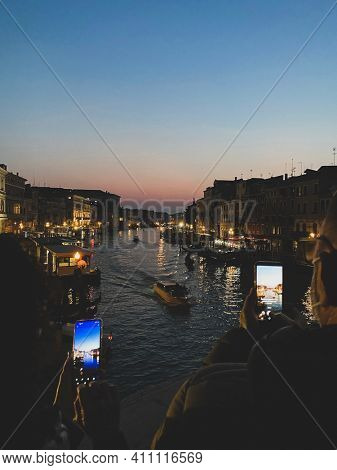 Two tourists taking a photo from the famous Rialto bridge Venice in the evening, grand canal.