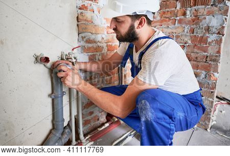 Horizontal Snapshot Of Young Plumber, Wearing Blue Uniform And White Helmet Working With Sealant Fix