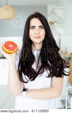 Portrait Of Happy Young Woman Holding Grapefruit In The Kitchen. Healthy Eating. Beauty, Cosmetics C