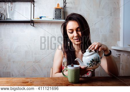 The Girl Eats A Sweet Dessert Sitting At The Table. High-calorie Breakfast
