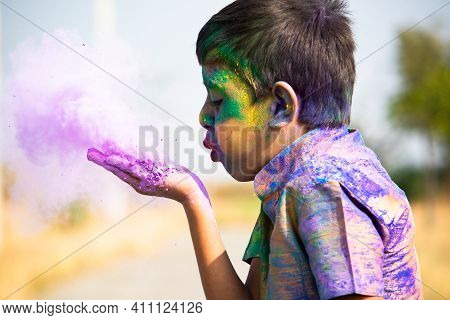 Kid Blowing Holi Colour Powder From Hand During Holi Festival Celebration - Concept Of Young Kids Ha