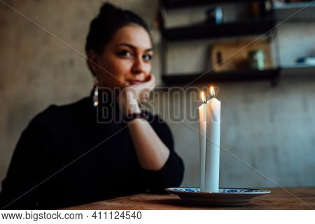 The Girl Is Guessing On A Lighted Candle And Cards, Predicting The Future And Fate