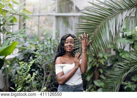 African Woman Model In Tropical Hothouse. The Portrait Of African American Female Model In Casual Ou