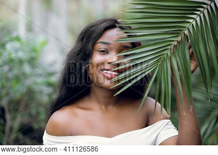 Fashion Tropical Portrait. Young Attractive Dark Skinned Woman Model In White Shirt, Holding In Hand