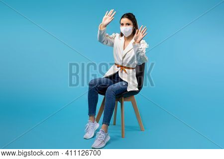 Young Female Student In A Protective Mask Sits On A Chair Isolated On A Blue Background, Gestures Wi