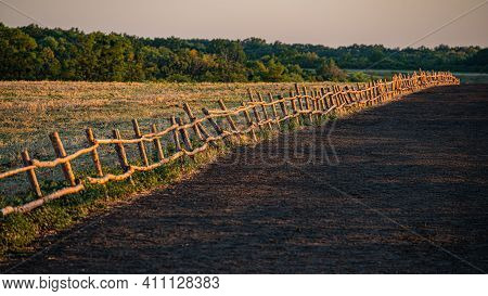 Wooden Fence In The Livestock Feeding Field, Panoramic Evening Landscape. Summer Season.