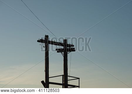 Silhouette Of An Old Wooden Power Line Support Against The Background Of The Evening Sky. Summer Sea