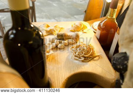 Some Types Of Dough Products Lie On A Wooden Board Surrounded By Bottles Of Wine