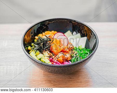 Poke Bowl With Salmon, Avocado, Radish, Corn, Seaweed, Peas, Nori, Daikon, Sesame Seeds. Top View. A