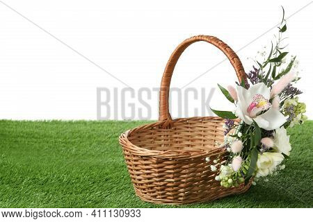 Wicker Basket Decorated With Beautiful Flowers On Green Grass Against White Background, Space For Te