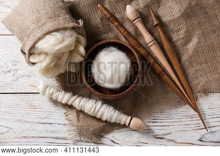 Soft Wool And Spindles On White Wooden Table, Flat Lay