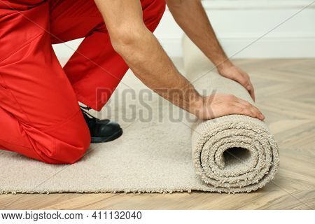 Worker Rolling Out New Carpet Flooring Indoors, Closeup
