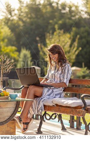 Female Freelancer Sitting At Bench On Terrace In Backyard, Working On Laptop Computer, Drinking Coff