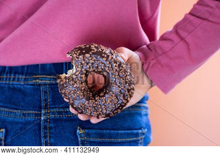 Child With Donut Behind Her Back, Close Up. Cheat Meal, Breaking The Diet, Unhealthy Eating Concept.