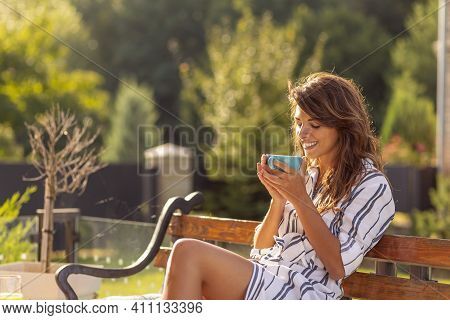 Beautiful Young Woman Relaxing On The Terrace In The Backyard Of Her Home, Drinking Morning Coffee A
