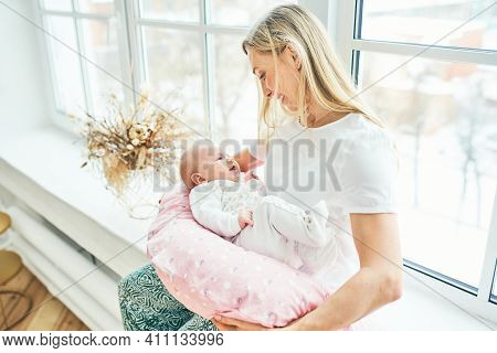 A Young Mother With A Baby At The Window Admires Her Beautiful Daughter. Care And Motherhood.