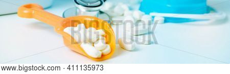 some pills in an orange beach shovel next to a blue beach pail, on the desk of a doctors office, depicting the medical assistance in summer, in a panoramic format to use as web banner or header
