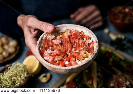 closeup of a young man with a rustic bowl of tomato salad in his hand, at a table next to a tray with freshly made vegan appetizers with different vegan toppings