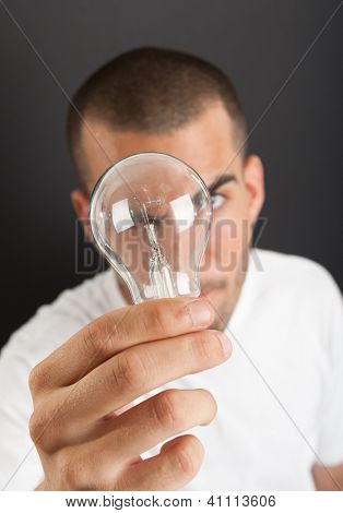 Man with a happy eureka expression holding a light bulb
